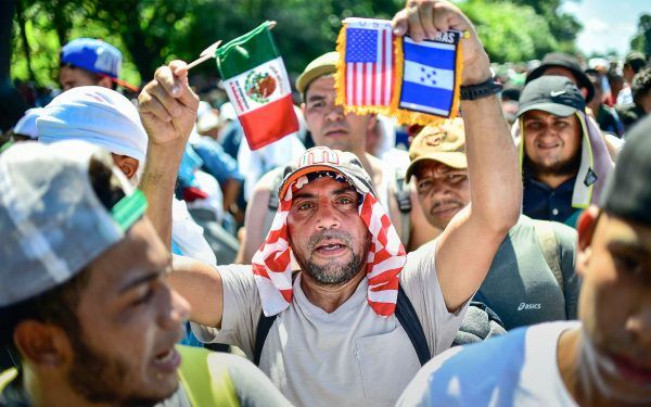 A migrant heading in a caravan to the US, holds Mexican, US and Honduran national flags on the road linking Ciudad Hidalgo and Tapachula, Chiapas state, Mexico, on October 21, 2018. - Thousands of Honduran migrants resumed their march toward the United States on Sunday from the southern Mexican city of Ciudad Hidalgo, AFP journalists at the scene said. (Photo by Pedro Pardo / AFP) (Photo credit should read PEDRO PARDO/AFP/Getty Images)