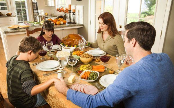 Family-Holding-Hands-In-Prayer-Prior-To-Thanksgiving-Feast