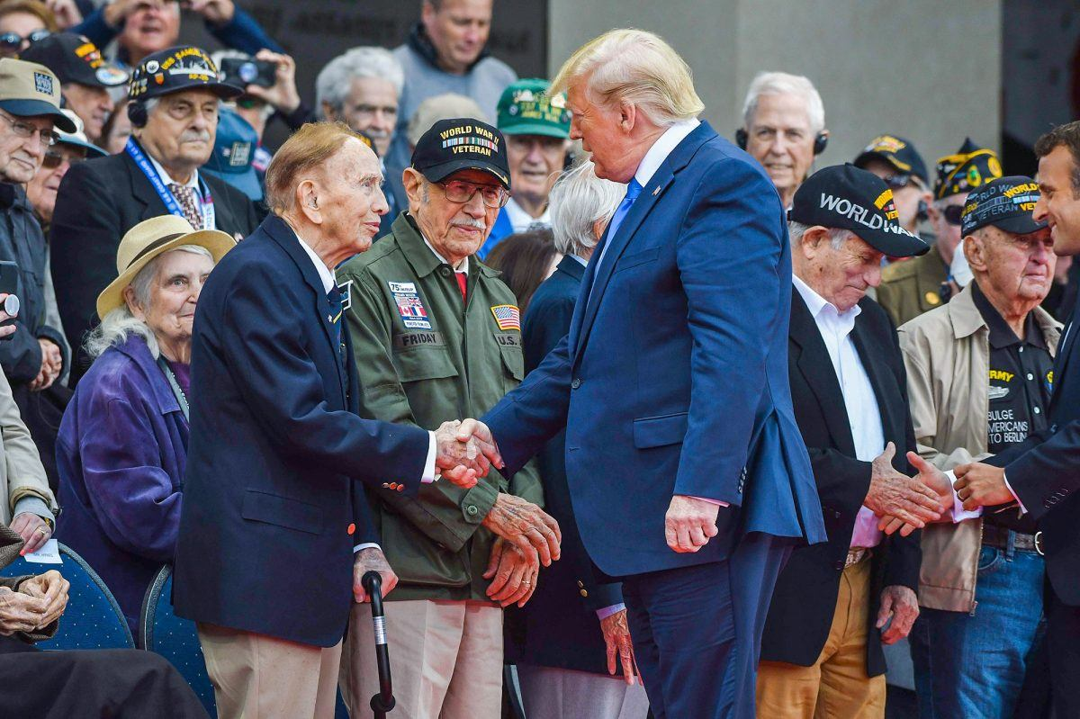 President Donald J. Trump talks with World War II veterans attending the 75th D-Day anniversary ceremony at the Normandy American Cemetery and Memorial in Colleville-sur-Mer, France, June 6, 2019.